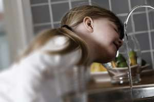 Child drinking safe water at home