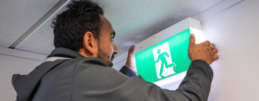 Technician performing emergency lighting maintenance