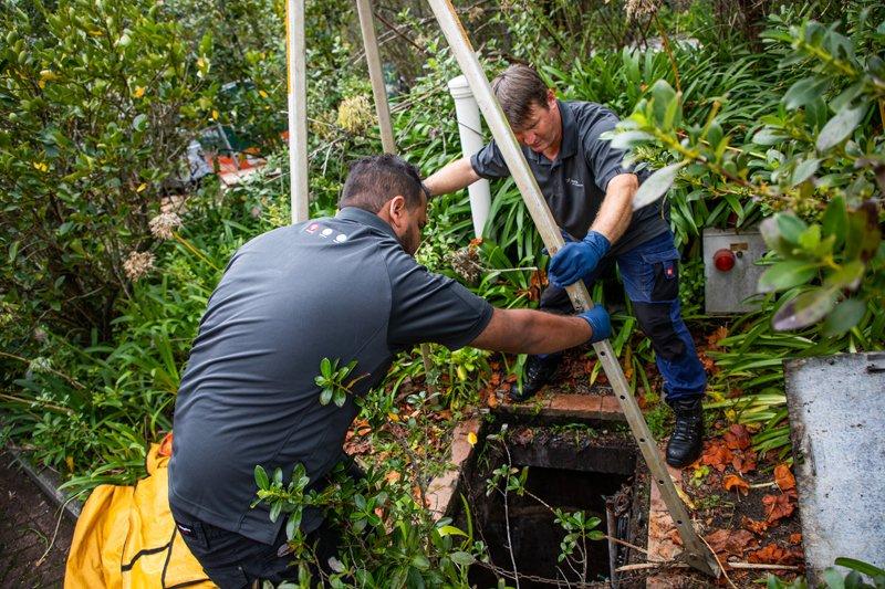 Technicians inspecting a sewage pit