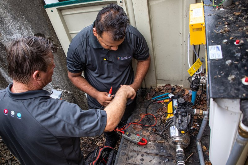 Technicians servicing home pressure and filter system