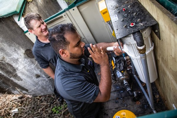 Technician servicing a home pressure and filtration system pump support