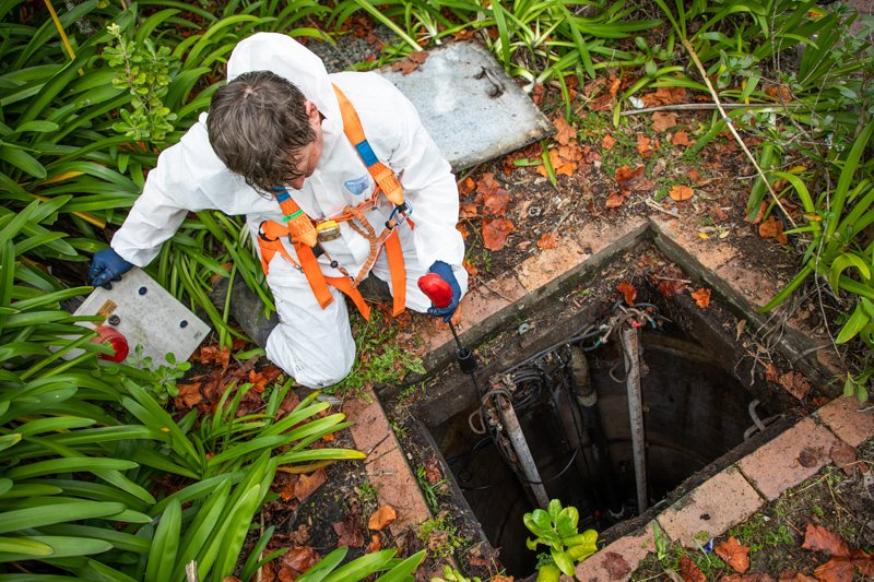 Technician inspecting sewage pit