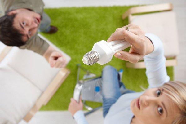 Man and woman changing lightbulb
